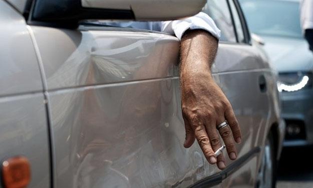 Hombre con la mano apoyada en la ventanilla del coche y fumando.